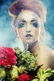 拿着花的美丽的redhair妇女 免版税库存图片