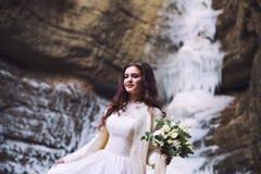 拿着花的花束从玫瑰的性感的新娘在冰川的背景 免版税库存图片