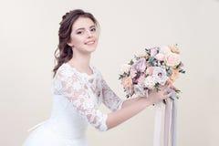 拿着花的花束可爱的微笑的妇女佩带在背景隔绝的豪华婚礼礼服 库存照片