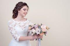 拿着花的花束可爱的微笑的妇女佩带在背景隔绝的豪华婚礼礼服 库存图片
