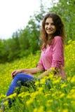 拿着花的花束向日葵的领域的可爱的女孩 免版税库存照片
