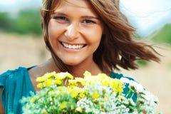 拿着花的花束女孩 免版税库存图片
