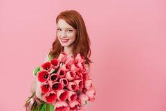 拿着花的花束微笑的姜妇女 免版税库存照片