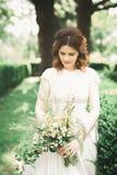 拿着花的花束新娘在公园 婚姻 图库摄影
