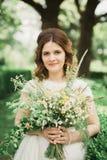 拿着花的花束新娘在公园 婚姻 库存图片