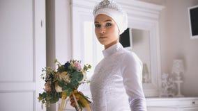 拿着花的花束白色婚礼礼服的回教新娘手中 图库摄影