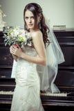 拿着花的花束年轻美丽的新娘。 免版税图库摄影