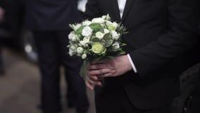 拿着花的英俊的商人 拿着花的花束衣服的新郎 婚礼钮扣眼上插的花 典雅的人 影视素材