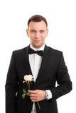 拿着花的衣服的英俊的年轻人 库存照片