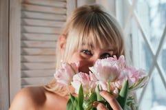 拿着花的被弄脏的观点的妇女由窗口,微笑 库存图片