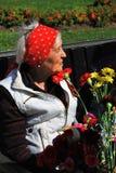 拿着花的退役军人妇女的画象 免版税库存照片