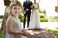 拿着花的逗人喜爱的女孩在婚礼 免版税库存图片