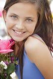 拿着花花束的逗人喜爱的女孩在市场上 免版税库存图片