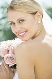 拿着花花束的露背的婚礼礼服的新娘 库存图片