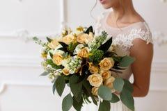 拿着花,婚姻的花束的花束在一个土气样式的新娘 免版税库存照片