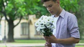 拿着花,等待的女朋友在日期,紧张,不安全的少年的男孩 股票录像