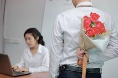 拿着英国兰开斯特家族族徽的花束在他的后的年轻亚裔商人为女朋友在情人节 爱和浪漫史在工作 库存照片