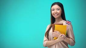 拿着英国旗子书,教育的快乐的妇女海外,学会语言 股票录像