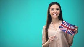 拿着英国旗子的微笑的妇女,准备好学会外国语 股票录像