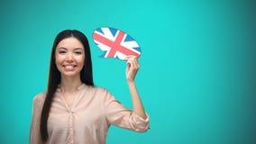 拿着英国旗子讲话泡影的微笑的女孩,学会语言,旅行想法 股票视频