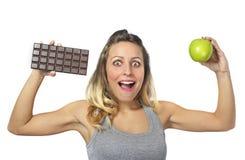 拿着苹果和巧克力块在健康果子的可爱的妇女对甜速食诱惑 免版税图库摄影