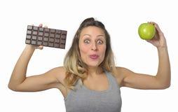 拿着苹果和巧克力块在健康果子的可爱的妇女对甜速食诱惑 免版税库存照片