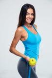 拿着苹果和测量磁带的健身妇女 免版税库存照片