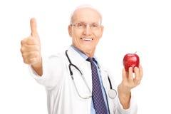拿着苹果和给赞许的成熟医生 库存照片