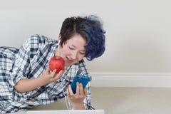拿着苹果的十几岁的女孩,当使用她的手机时和听 免版税库存图片