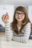 拿着苹果的十几岁的女孩画象,当坐在桌上在房子里时 免版税图库摄影
