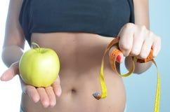 拿着苹果的少妇测量的身体 免版税图库摄影