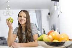 拿着苹果的微笑的女孩画象,当坐在桌上在房子里时 免版税库存照片