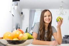 拿着苹果的微笑的女孩画象,当坐在桌上在房子里时 库存图片