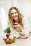 拿着苹果的微笑的妇女 库存图片
