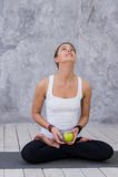 拿着苹果的愉快的体育妇女坐在灰色背景的瑜伽席子 免版税库存照片