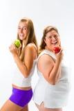 拿着苹果的稀薄和肥胖妇女手中 免版税图库摄影