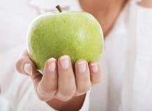 拿着苹果的美丽的年轻女商人。 库存图片