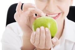 拿着苹果的年轻美丽的女商人。 免版税图库摄影