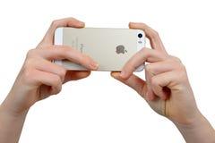 拿着苹果计算机iPhone 5S巧妙的电话的妇女手 库存图片