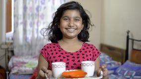 拿着茶杯和快餐在盘子正面图画象的逗人喜爱的矮小的愉快的印度亚裔白种人女孩孩子 影视素材
