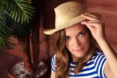 拿着草帽和坐在s的木房子附近的白肤金发的夫人 免版税库存照片