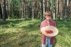 拿着草帽的男孩有很多红色wildberries 免版税库存照片
