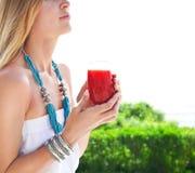 拿着草莓汁的杯的妇女 免版税图库摄影