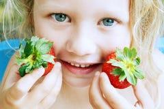 拿着草莓的女孩 免版税库存图片