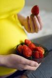 拿着草莓的怀孕的女孩 免版税库存图片