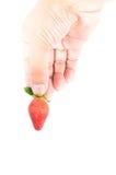 拿着草莓的手 库存照片