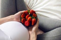 拿着草莓的板材怀孕的女孩 库存图片