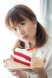 拿着草莓蛋糕的逗人喜爱的亚裔少年 库存照片