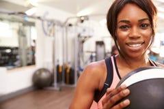拿着药丸的一名微笑的妇女的画象在健身房,拷贝空间 库存图片