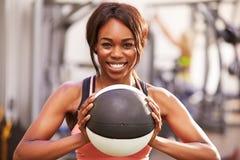 拿着药丸的一名微笑的妇女的画象在健身房 免版税库存照片